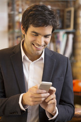 Handsome man using a cell phone in coffee bar, sms, message