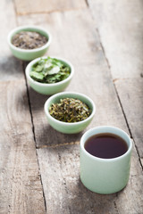 Different sorts of green tea in a green cup