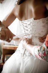 Closeup shot of bridesmaid tying corset on bridal dress