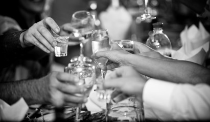 photo of hands clinking glasses with vodka at party