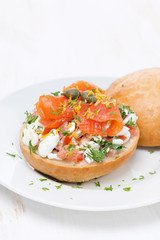 sandwich with cheese, tomato and salmon on the plate, vertical
