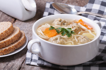 Soup with noodles and meatballs on the table