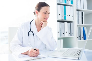 Doctor writing while using laptop