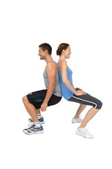 Side view of a fit young couple doing squats