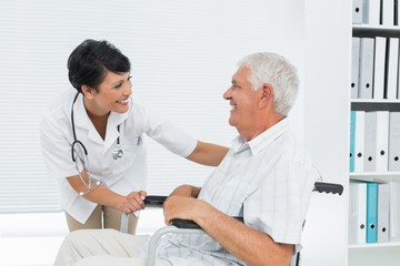 Female doctor talking to senior patient in wheelchair