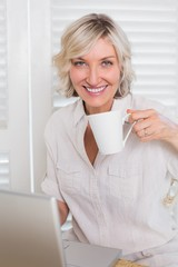 Woman drinking coffee while using laptop at home
