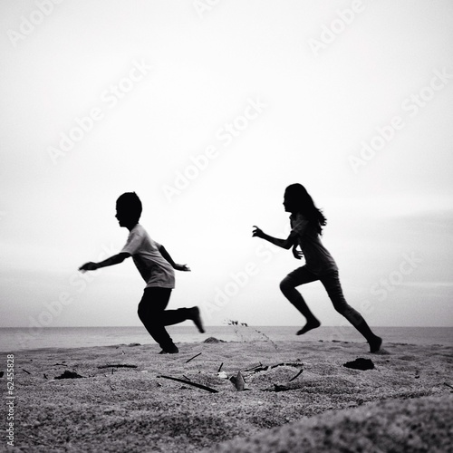 Two Kids Running Silhouettes On The Beach