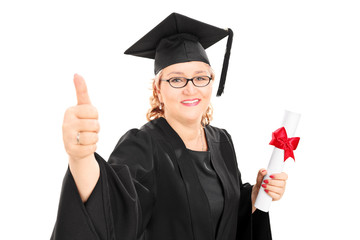Mature female student holding a diploma and giving thumb up