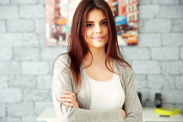 Young happy businesswoman with arms folded standing at office