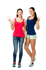 two young women sitting and showing victory sign
