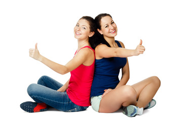 two young women sitting and showing ok sign