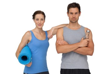 Portrait of a fit couple with exercise mat and water bottle