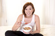 red haired happy woman eatting cereal and stawberries
