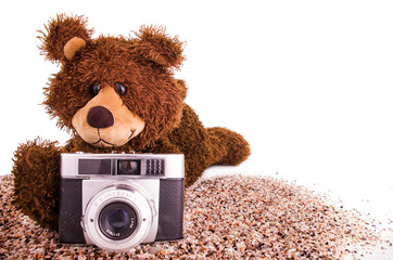 Cute teddy bear is with a camera on the sand