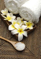 frangipani in bowl with towels and herbal salt on mat