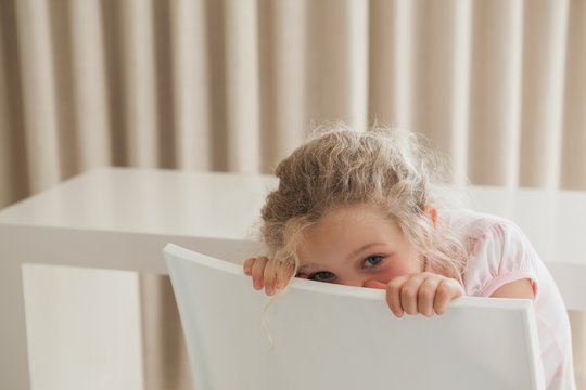 Cute girl hiding face behind chair