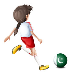 A girl kicking the ball with the flag of Pakistan