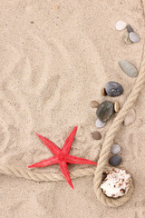 Starfishes and stones with rope on sand