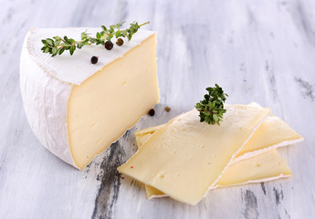 Tasty Camembert cheese with spices, on wooden table