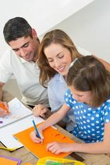 Parents looking at girl drawing