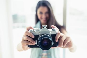 Stylish young woman taking a photo at camera