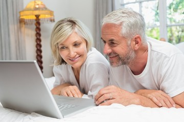 Happy mature couple using laptop in bed