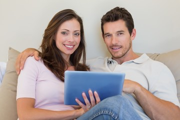 Relaxed couple using digital tablet in living room
