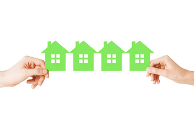 Wall Mural - man and woman hands with many green paper houses