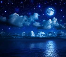 super moon in starry sky with clouds and sea