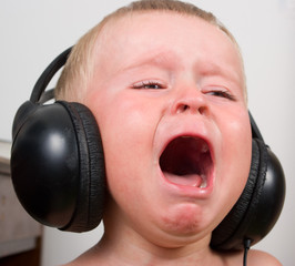 Little boy listening in stereo headphones crying and screaming