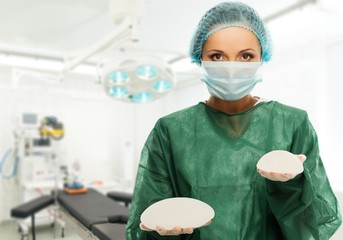 Plastic surgeon woman holding different size silicon breast