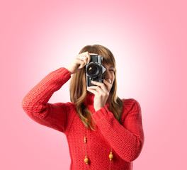 Girl taking a picture over pink background