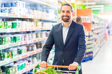 Kunde schiebt Einkaufswagen in Supermarkt
