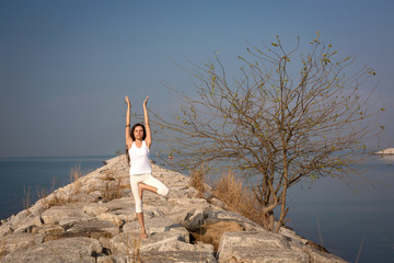 Woman practicing yoga on the beach and tree. Vrksasana