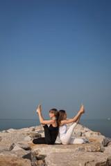 Beautiful women practicing yoga on the beach, Krounchasana