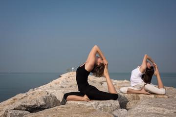 Beautiful young women practicing yoga on the beach. Kapotasana