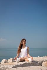 Beautiful woman in Lotus posture on the beach