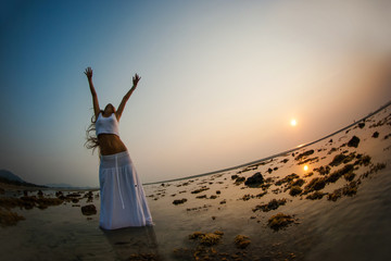 A beautiful woman is dancing on the beach at sunset