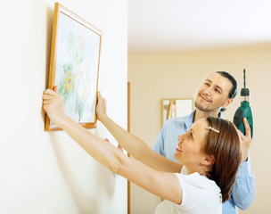 man and woman  hanging  art picture in frame on wall