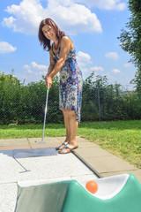 Frau spielt Minigolf