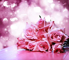 Beautiful pink roses on pink wooden table