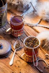 Fototapete - Warm leaf tea served in old-style