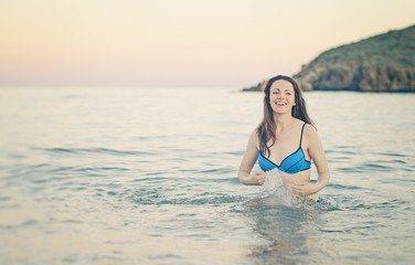Happy woman in the sea splashing water. Vintage effect.