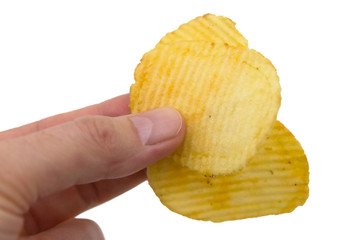 Rippled crisps held between fingers, ready to eat