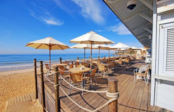 outdoor terrace cafe on sand beach, Portugal