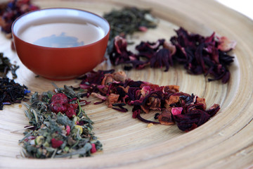 Different kinds of dry tea on dish close up