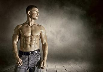 Bodybuilder posing on the outdoor grunge background
