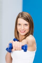 lächelnde frau trainiert mit kleinen gewichten
