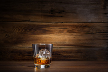 glass of whiskey with ice on a wooden background