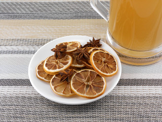 beer mug with cinnamon and lemon on white plate